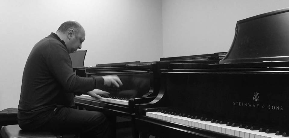 George Vatchnadze playing piano in his studio